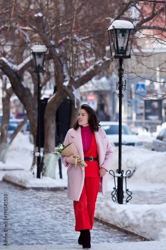 Poster girl walking around the city with a bouquet of flowers