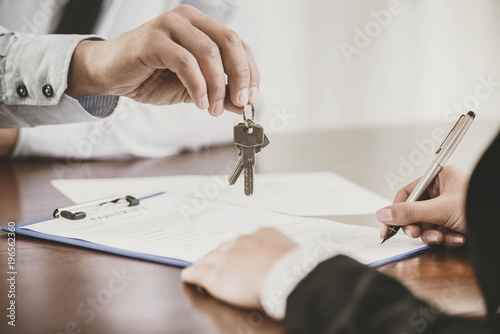 Young woman is signing financial contract with male realtor - 196562360