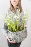 Lilies of the valley in a gray wicker basket. Fresh spring flowers as a gift. Cute girl holding a floral arrangement