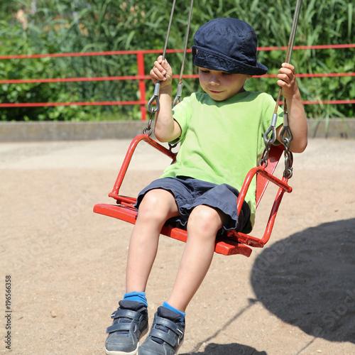 Foto op Aluminium Amusementspark kleiner Junge auf dem roten Sitz eines Kettenkarussels