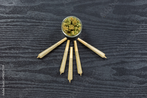 Foto Spatwand Apotheek Weed in glass jar with joints arranged on black textured surface