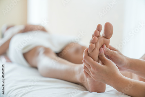 Plexiglas Pedicure Woman having a pedicure treatment at a spa or beauty salon with the pedicurist massaging the soles of her feet with a pumice stone to cleanse dead skin and stimulate the tissue