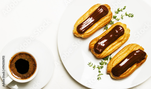 Poster Eclairs cakes and morning espresso coffee in a cup, unhealthy breakfast, white background, top view