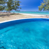 piscine à débordement sur fond de plage tropicale  - 196587563