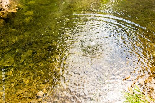 Koła na powierzchni wody z kamieniami na dole