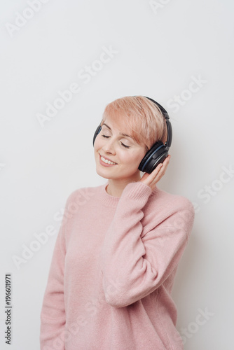 Blissful pretty woman listening to music - 196601971