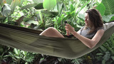 Woman using smartphone while sitting on hammock, exotic background - 196604929