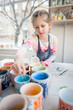 Young girl painting in pottery workshop using colourful paints and brush