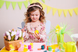 cute baby girl paints an egg on the background of the Easter decor. - 196616953