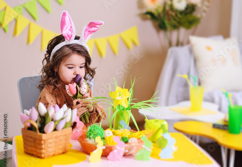 baby girl in rabbit ears sitting at table on background of Easter decor and toy colors of tulips
