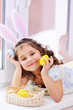 baby girl with rabbit ears with painted eggs in hands smiling on background of easter basket sitting near window