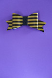 Black and golden striped bow tie over ultra violet background. - 196623186