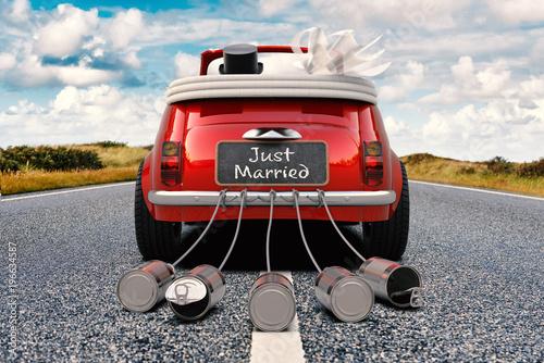 Ein frischvermähltes Brautpaar im Cabriolet auf einer Straße mit Just Married Schild und Blechdosen, Ansicht von hinten