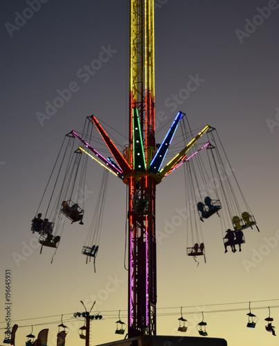 In de dag Amusementspark Carnival ride lit up at dusk, with people in swings up high.