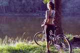 Girl cyclist  near the river - 196651383