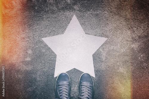 Foto Murales Sneakers on asphalt road with white star
