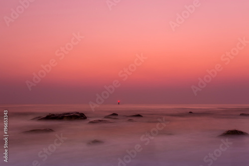 Foto op Canvas Crimson long exposure of the sunrise over the sea and rocks