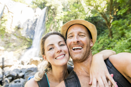 Happy couple taking selfie portrait at tropical waterfalls in summer vacation - 196655333