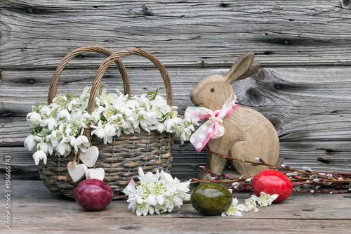 Fototapeta Ostern mit Märzenbecher im Weidenkorb-Osterhase und Ostereier rustikal auf Holz