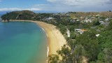 Wide drone shot of New Zealand beach with people sunbathing. - 196672167