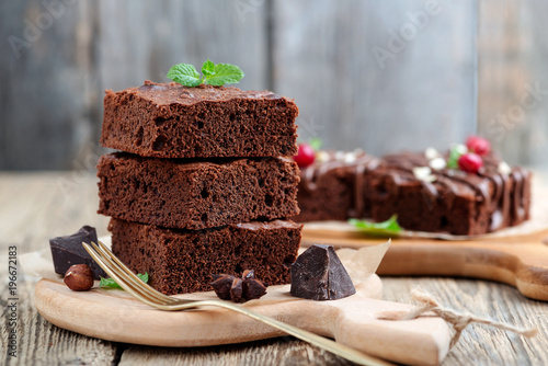 Chocolate brownie cake, dessert with nuts on wooden background.
