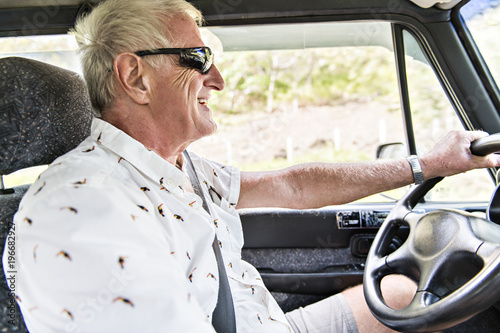 Wall mural mature senior man on his car drive on tropical country