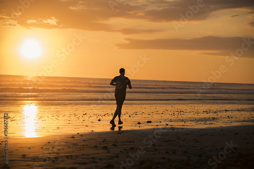 Fotobehang Jogging Jogger on a beach at sunset silouhaite
