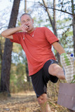 handsome middle aged man stretching outdoors - 196694528