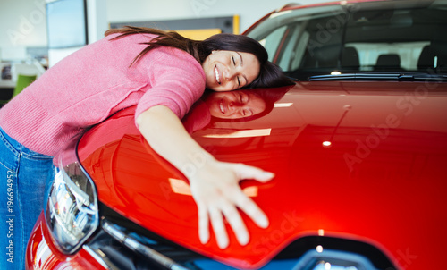 Wall mural Happy beautiful young woman buying a new car at the car showroom.