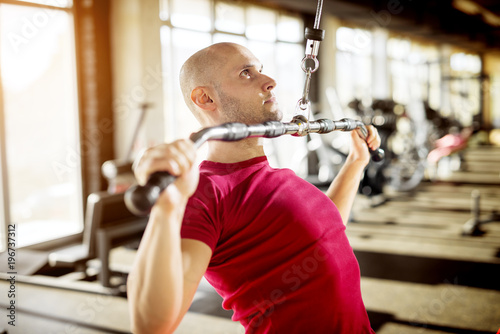 Wall mural Close up side view of motivated and focused strong muscular active healthy young bald man sitting on the bench and pulling the metal bar from the machine for back muscles.
