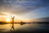 Colorful vunrise landscape over foggy River Thurne looking towards Thurne Mill Windmill