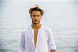 Handsome Young Man in Trendy Attire, on a Beach in a Sunny Summer Day, Wearing a White Shirt and Straw Hat