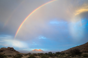 A double rainbow and approaching rain storm with clouds in the sky above the plains of Namibia with a mountain on the horizon