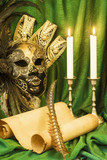 Literature concept, candle in a candlestick near a Venetian mask and a scroll of parchment on a green background