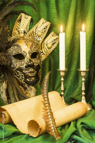 Foto op Canvas Venetie Literature concept, candle in a candlestick near a Venetian mask and a scroll of parchment on a green background