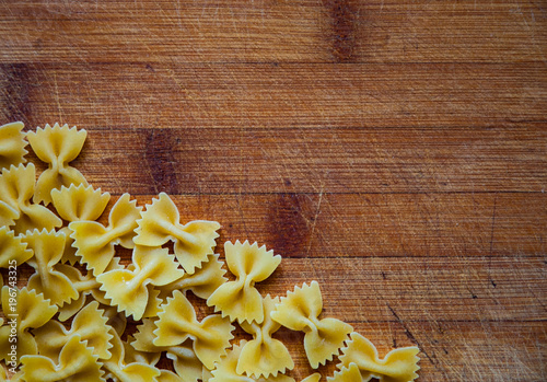 Foto op Aluminium Vlinders in Grunge pasta farfalle on wood background. Top view with copy space