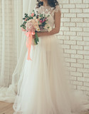 bride from a wedding bouquet near a white wall - 196770980