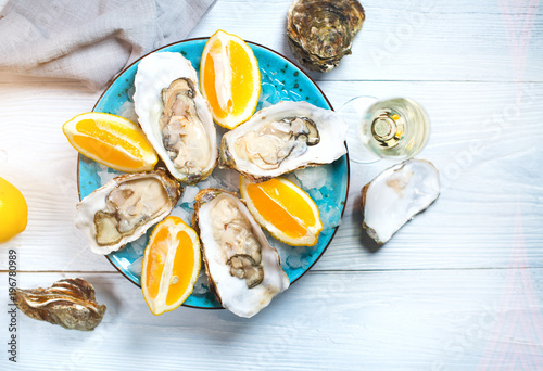 Fresh oysters close-up on blue plate, served table with oysters, lemon and champagne in restaurant. Gourmet food. Tabletop view