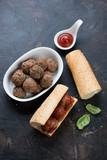 Homemade subs with baked beef meatballs on a dark brown stone background, elevated view, studio shot - 196783368