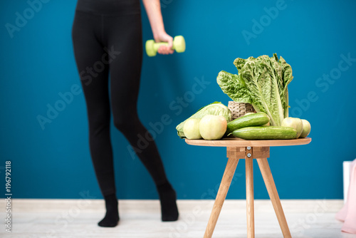 Sports female body with dumbbells and healthy green food on the blue wall background