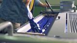 An employee is preparing blue paint in an industrial printing machine - 196794702