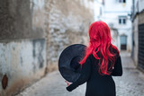 A small witch in a black dress with red hair is holding a hat in her hands and standing with his back against the backdrop of the street of the old city