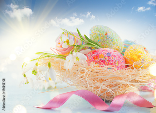 Easter holiday scene background. Traditional colorful eggs and spring flowers in the nest over blue sky, border design