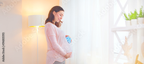 Pregnant woman touching her belly and playing with little baby shoes. Happy pregnant middle aged mother at home. Pregnancy concept