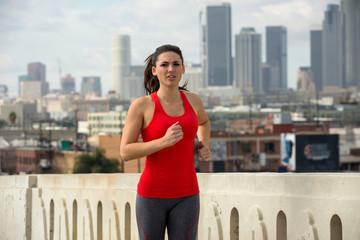 Female runner jogging with city skyline in the background © elnariz