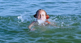 Danger in the water: swim safety rules. Young girl learn to swim  in sea.