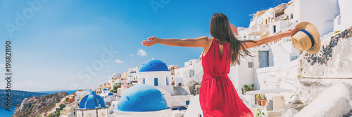 Leinwanddruck Bild Europe travel vacation fun summer woman feeling free dancing with arms open in freedom at Oia, Santorini, Greece island. Carefree girl tourist banner panorama.