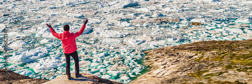 Greenland travel hiker tourist man happy with arms up in success. Adventure expedition in the arctic, texture of blue ice from icebergs in ocean. Banner panorama.