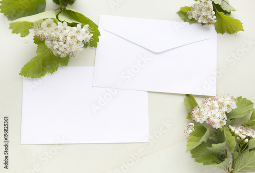 Craft paper sheets and white envelope. Blank card with spring green leaves and white flowers. Mockup design. Top view with copy space.