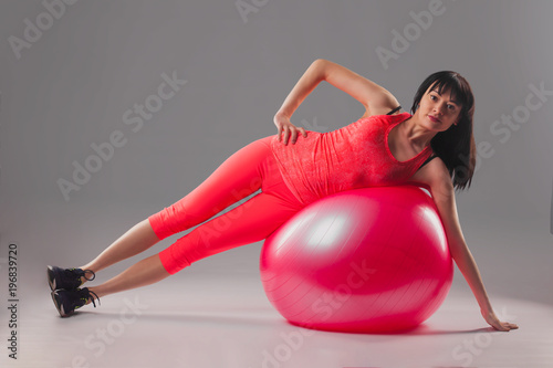 cute brunette woman doing exercises with fitball.